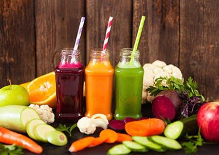 Sucos em garrafas de vidro sobre mesa com vários vegetais, como penino, cenoura e laranja fatiados