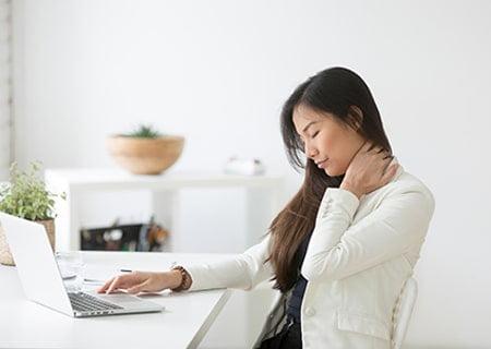 Mulher sentada em frente a notebook. Uma mão está no teclado e, a outra, ela pressiona a lateral do pescoço. Ela está com os olhos fechados, indicando sensação de dor.