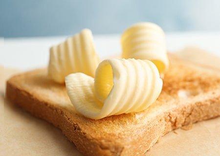 Fatia de torrada com lascas de manteiga por cima
