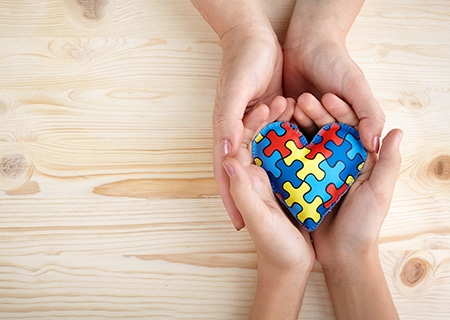 Mãos segurando coração de quebra-cabeça, símbolo em alusão ao autismo
