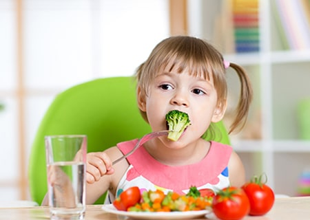 Menina sentada com um prato de verduras à frente. Ela segura um brócolis com o garfo e o leva à boca.