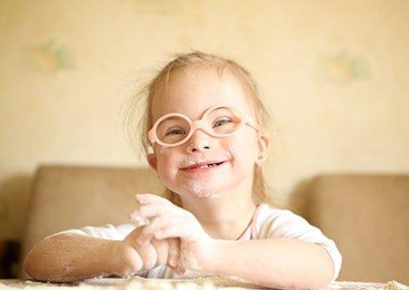 Garotinha com síndrome de Down sorri. Ela usa óculos de armação laranja e redonda e tem as mãos sujas de farinha