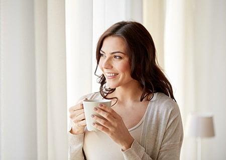 Mulher segurando caneca, sorrindo e olhando para o lado. Ela tem cabelos pretos, lisos e veste uma blusa de manga comprida branca. Ao fundo, uma cortina branca.