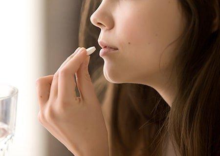 Mulher com deficiência de vitamina D levando à boca uma pílula branca de suplemento do nutriente.