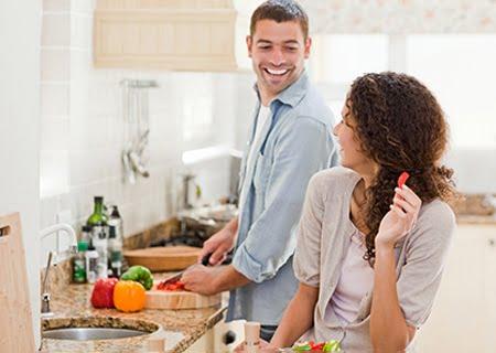 Casal cozinhando, se olhando e sorrindo