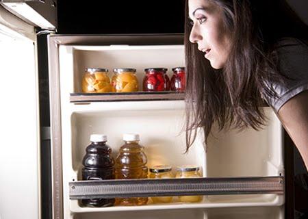 Mulher olhando a geladeira