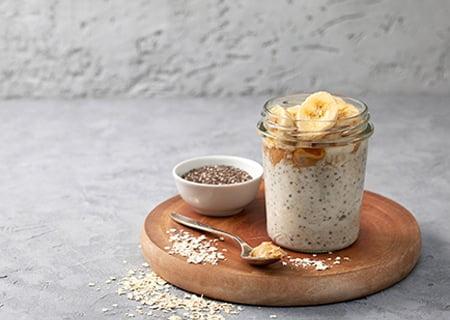Overnight oats em pote de vidro sobre mesa. Ele está em cima de tábua redonda de madeira, com uma colher cheia de aveia ao lado e grãos de aveia ao redor e um pote branco pequeno.