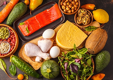Mesa com vários alimentos como frango, peixes, sementes e queijo