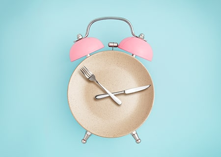 Relógio em forma de prato, com um garfo e uma faca em cima