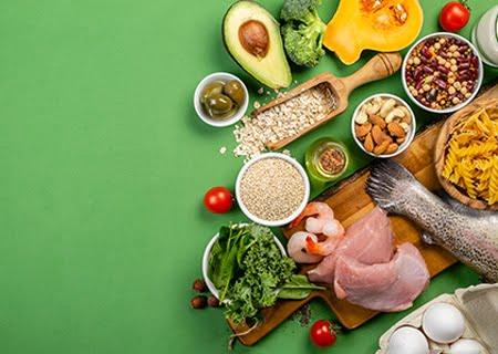 Mesa com diversos alimentos, como abacate, carnes e brócolis, itens que fazem parte da alimentação para controlar pressão alta.
