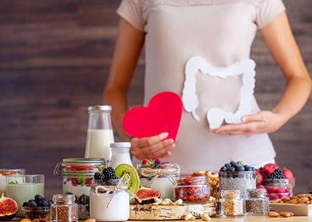 Silhueta de mulher segurando um intestino de papel com uma mão e, com outra, um coração de papel. Ela está atrás de uma mesa repleta de diversos alimentos, como frutas e leite em jarras de vidro.