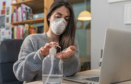 Mulher com máscara, em casa, e limpando as mãos com álcool gel