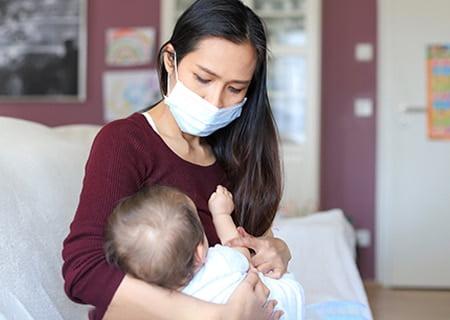 Mulher amamentando bebê. Ela usa uma máscara
