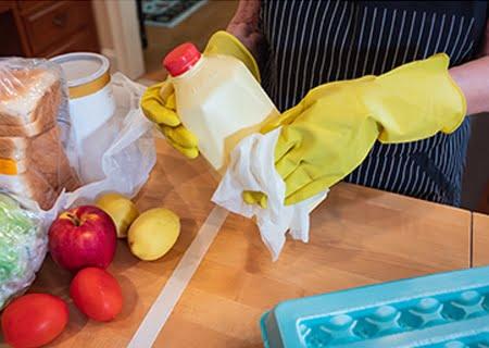 Alimentos sobre mesa e pessoa com luvas de borracha limpando garrafa com um pano.