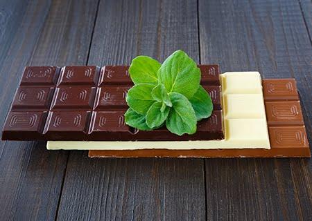 Mesa com tabletes de chocolate ao leite, branco e amargo. Em cima deles, folhas de hortelã.