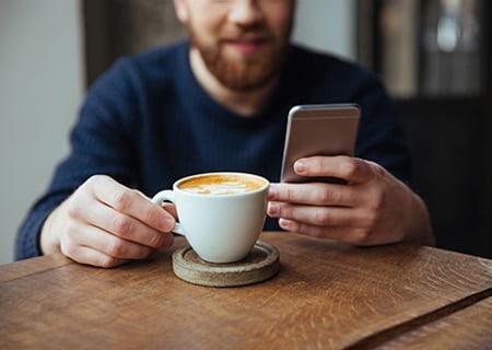 Homem segurando uma xícara de café com uma mão e, com a outra, olha o celular