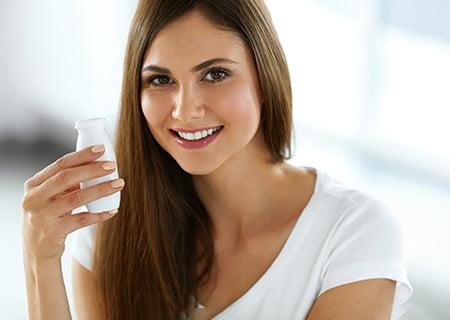 Mulher sorridente segurando garrafa de vidro. Ela tem cabelos lisos castanhos e veste uma camiseta branca.