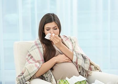 Mulher grávida sentada. Ela está com um cobertor xadrez nas costas e segura um lenço de papel no nariz. A outra mão apóia sobre a barriga.