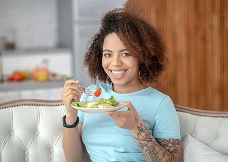 Mulher com tatuagem comendo prato de salada