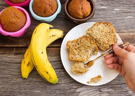 Mesa com muffins de banana, bananas e um prato com pedaços da receita e uma mão segurando um garfo o pegando