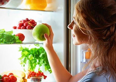 Mulher sorridente abrindo geladeira e pegando uma maçã verde
