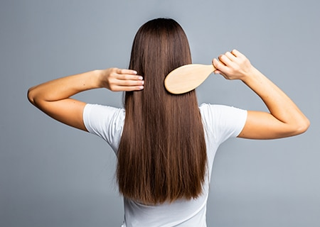 Mulher de costas penteando os cabelos com uma escova. <a href='https://br.freepik.com/fotos-vetores-gratis/mulher'>Mulher foto criado por diana.grytsku - br.freepik.com</a>