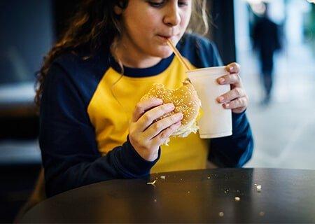 Menina sentada comendo hambúrguer e tomando refrigerante. <a href='https://br.freepik.com/fotos-vetores-gratis/alimento'>Alimento foto criado por rawpixel.com - br.freepik.com</a>