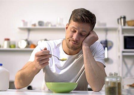 Homem olhando para uma colher com olhar de quem não quer comer.