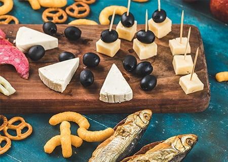 Mesa com alimentos ricos em sódio, como azeitonas, queijos, salgadinhos e peixes em conserva. Crédito da imagem: azerbaijan_stockers/Freepik.