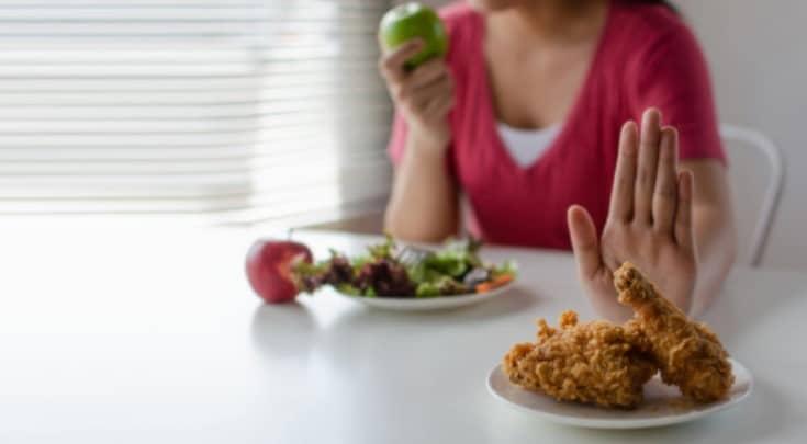 Mulher sentada à mesa comendo uma maçã verde. Na frente dela, um prato de salada. Mais à frente, um prato de carne frita, que ela recusa com a mão em sinal de recusa.