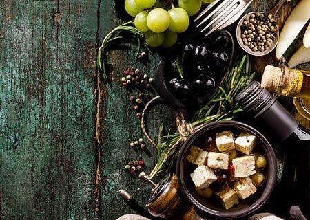 Mesa com uvas, queijos e azeites, alimentos que fazem parte da dieta mediterrânea. Crédito da imagem: valeria_aksakova/Freepik.
