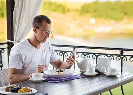 Homem olhando para o celular enquanto come