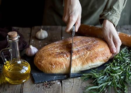 Pão sobre mesa ao lado de ramo de alecrim. Uma pessoa corta o pão ao meio.