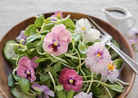 Tigela com salada de folhas, brotos e flores