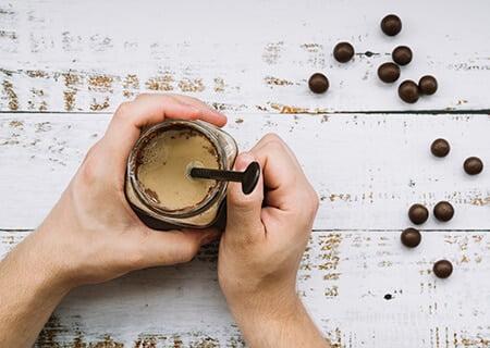 Mãos segurando copo de smoothie