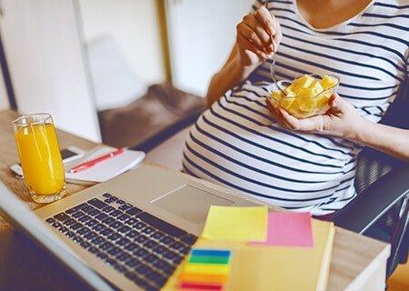 Mulher grávida sentada em frente a computador comendo laranja em pote