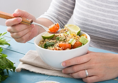Pessoa comendo bowl com verduras e grãos