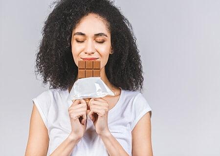 Mulher segura barra de chocolate com as duas mãos em frente à boca. Ela tem os olhos fechados e sorri.