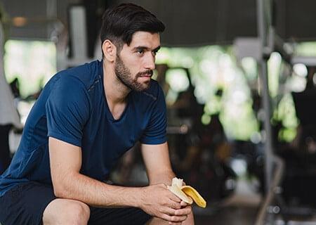 Homem sentado comendo banana