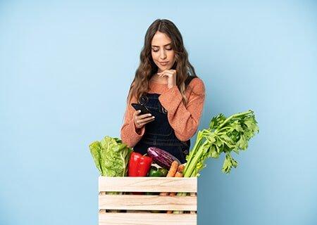 Mulher atrás de caixa de madeira com verduras olhando o celular. Ela está com a mão no queixo e expressão pensativa
