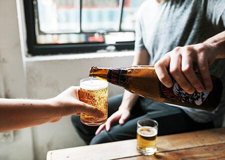 Homem servindo cerveja para outra pessoa
