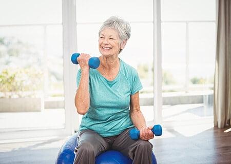 Idosa se exercitando sentada em bola de pilates e fazendo exercícios de braço com halteres.