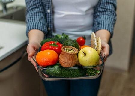 Pessoa segurando pote de vidro com diversos alimentos como frutas e vegetais