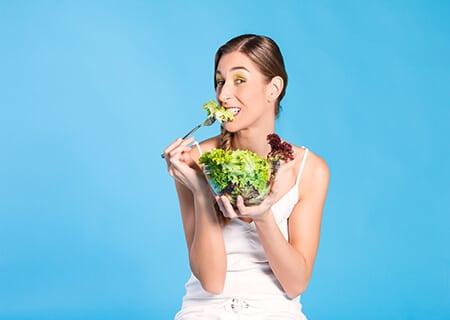 Moça comendo salada