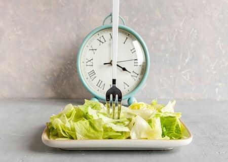 Prato de salada com garfo espetado e relógio de ponteiro ao fundo.
