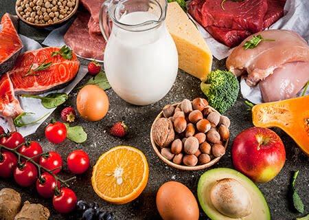 Mesa com diversos alimentos como leite, laranja, ovo, abacate, tomates-cereja e grãos