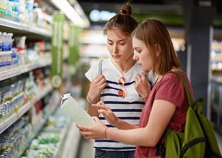 Mulheres no supermercado observando rótulo de alimento