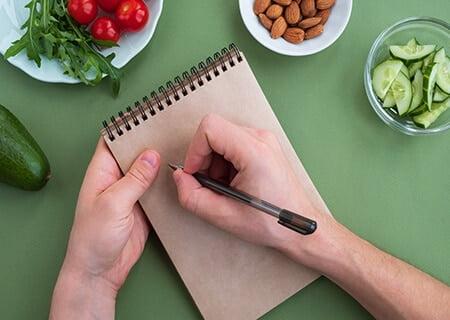 Mão anotando em caderneta sobre mesa com bowls de alimentos