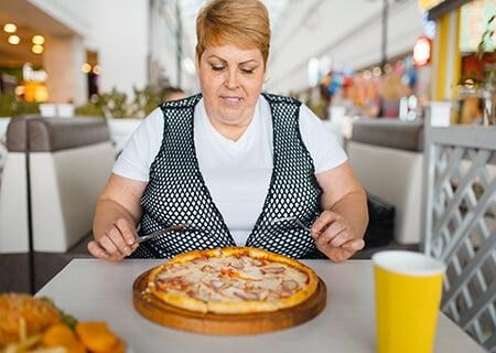 Mulher comendo pizza. Um dos fatores de risco para obesidade é a alimentação com excesso de gorduras.