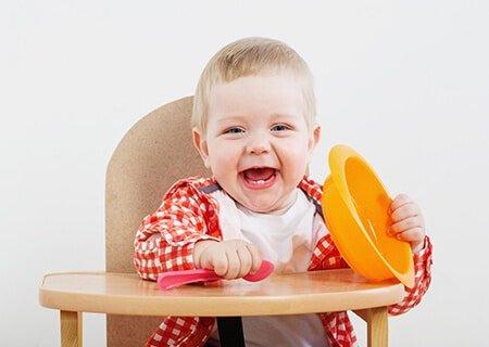 Criança segurando prato e talher e sorrindo